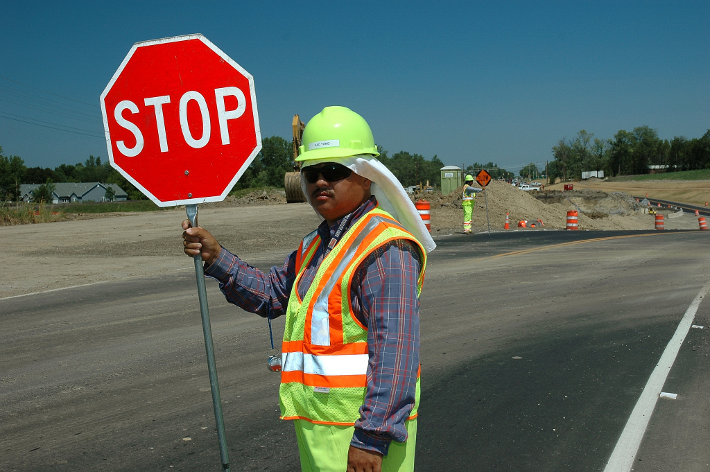 MnDOT employee at work site using a stop sign to control traffic